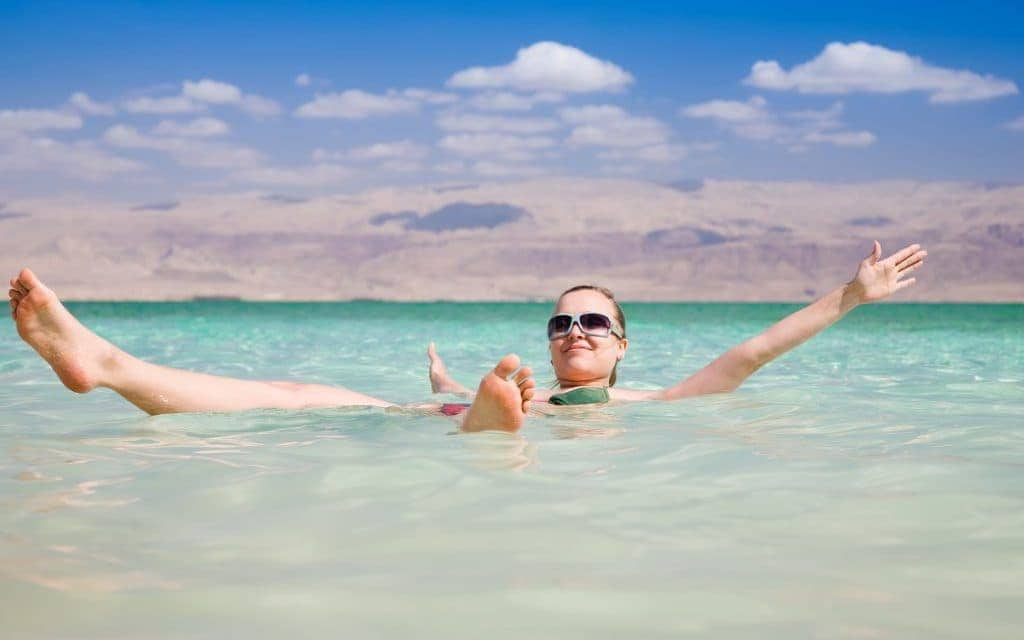 Woman floating on the salty waters of the Dead Sea