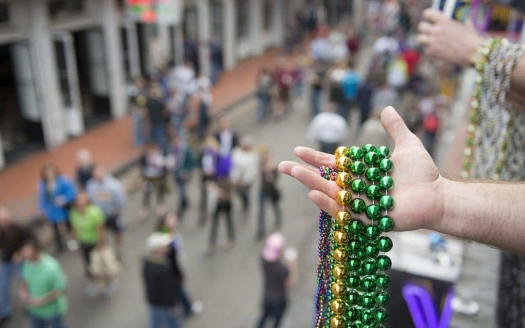 Mardi Gras beads in hand above Bourbon Street