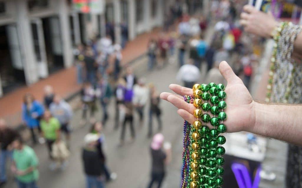 Mardi Gras beads in hand above Bourbon Street