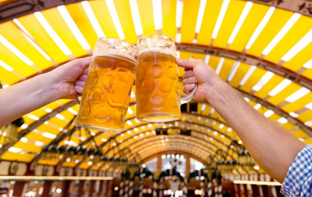 Two people clinking beer glasses at the Oktoberfest