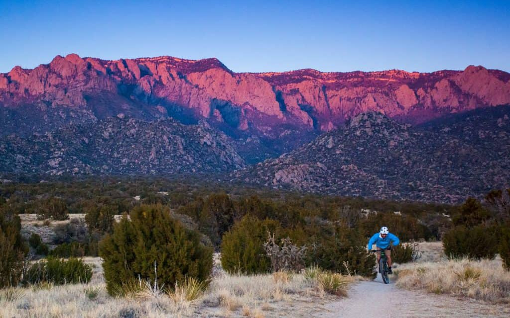 mountain biking man pedals through the desert mountain landscape as the sunset hits the mountains. such beautiful nature scenery and outdoor sports and recreation can be found when visiting new mexico, the land of enchantment. horizontal composition. sandia mountains. albuquerque, new mexico.