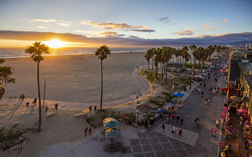 Tourists walking on footpath by Venice beach during sunset