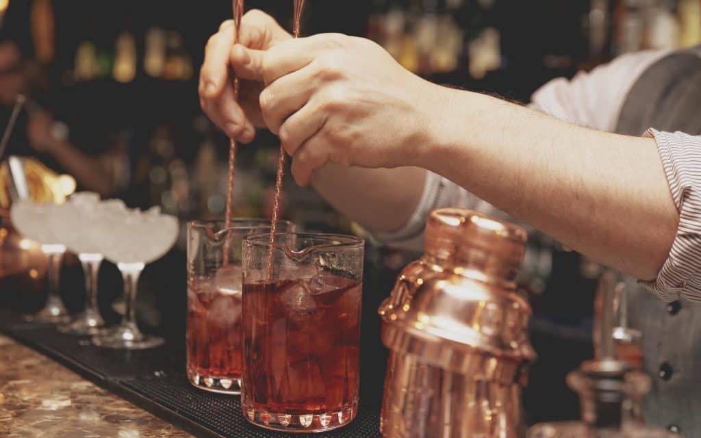 Bartender is stirring cocktails on bar counter