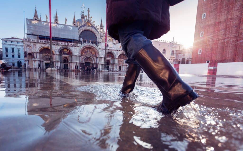 woman in rubber boots walking over St. Mark's Square in Venice