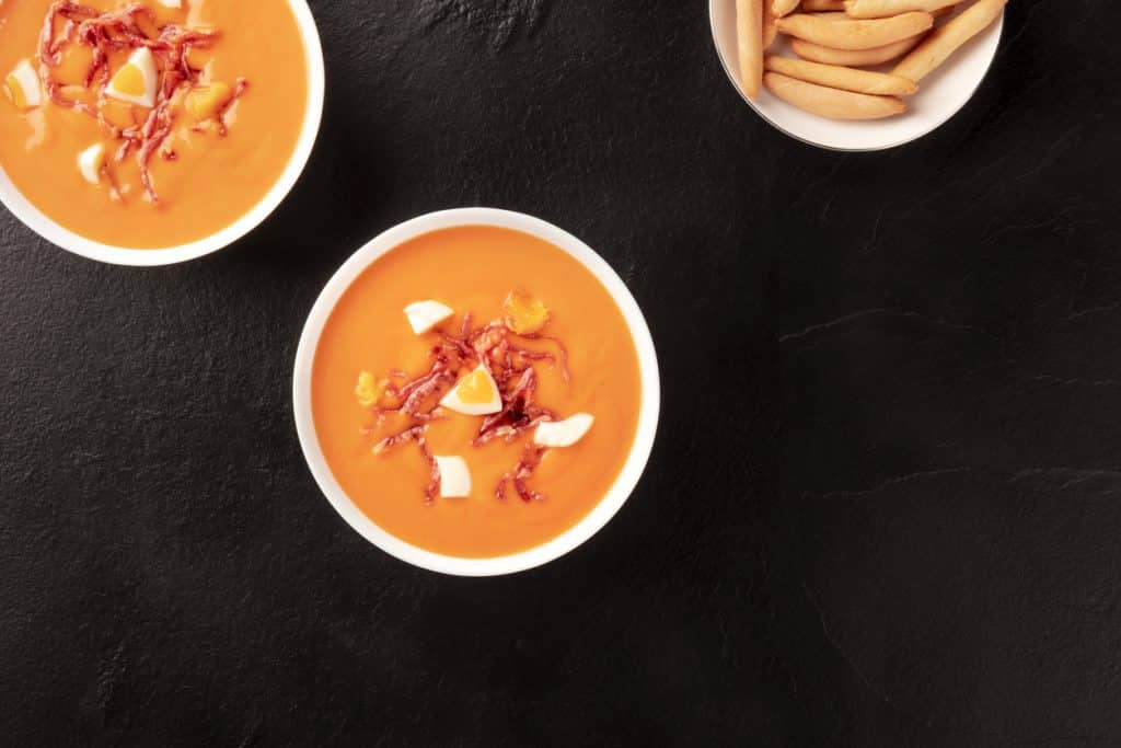 Salmorejo, Spanish cold soup, shot from above on a black background
