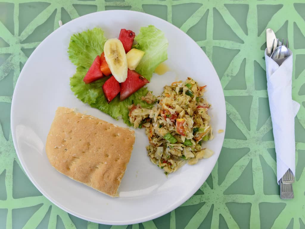 Salt fish and bake for breakfast in Tobago. Local caribbean dish served on a white plate and green table.