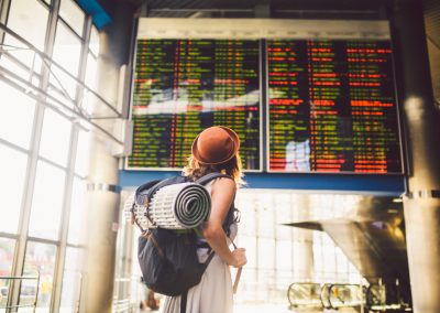 Theme travel public transport. young woman standing with back in dress and hat behind backpack and camping equipment for sleeping, insulating mat looks schedule on scoreboard airport station