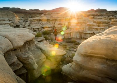 Backpacker Hiking In Hoodoo Wash In Bisti Badlands Wilderness Area New Mexico At Sunrise