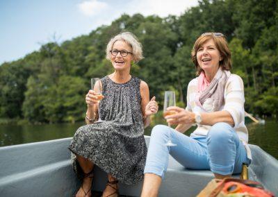 Cheerful women enjoying champagne on rowboat